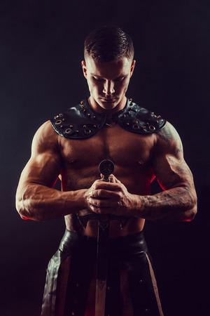 Ritratto di bel gladiatore muscolare con la spada. Lo studio ha sparato. Sfondo nero.