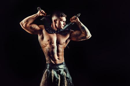 두 칼으로 잘 생긴 근육 검투사의 초상화입니다. 스튜디오 촬영. 검정색 배경입니다.