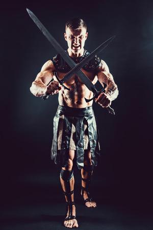 Portrait of handsome muscular gladiator crossed two swords. Studio shot. Black background. Scream.