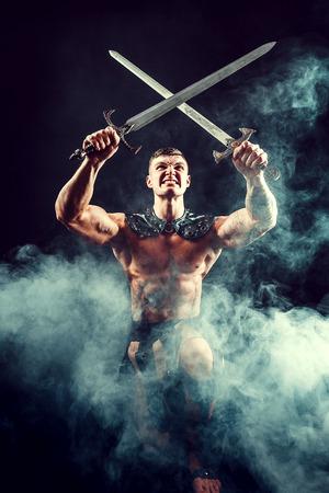 Aggressive expressive warrior crossing swords above head posing in smoke.