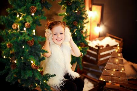 Nettes kleines Mädchen in den Pelzohrenschützern, die nahe Weihnachtsbaum sitzen und nett lächeln. Standard-Bild - 90365171