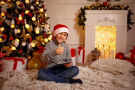 Happy-looking boy in Christmas hat sitting near Christmas tree, holding tablet and gesturing thumb up.