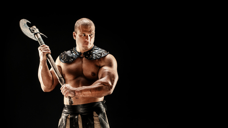 Severe barbarian in leather costume with axe. Studio shot. Black background. Stock Photo