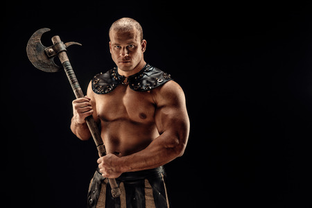 Severe barbarian in leather costume with axe. Studio shot. Black background. Banco de Imagens