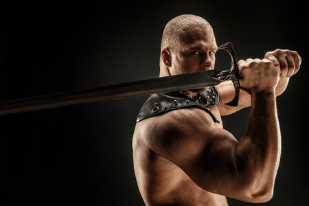 Severe barbarian in leather costume with sword. Portrait of balded muscular gladiator. Studio shot. Black background. Stockfoto