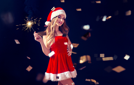 Young bright woman wearing stylish red dress of Christmas costume posing flirty with sparkler in confetti.
