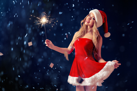 Young beautiful coquettish blonde wearing seductive red dress for Christmas posing at camera with burning sparkler.
