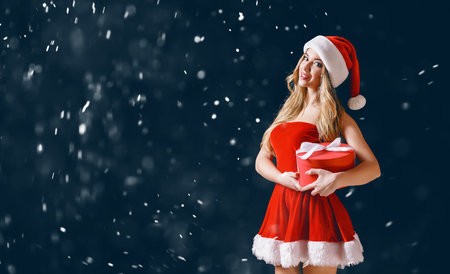 Attractive young model in Santa sexual dress and hat looking excited while posing with Christmas present. Stock Photo - 91868930