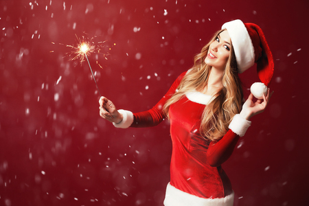Stylish blonde in alluring dress for Christmas holding burning sparkler and looking sensually at camera.