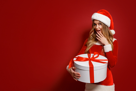 Attractive young model in Santa sexual dress and hat looking excited while posing with Christmas present.