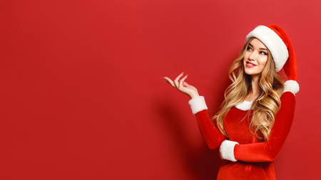 Young blonde in Santa female costume posing sensually at camera looking confident on red. Copyspace