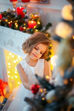 Cute little girl in white tender beautiful dress standing in brightly decorated room and holding Christmas decoration. Stock Photo