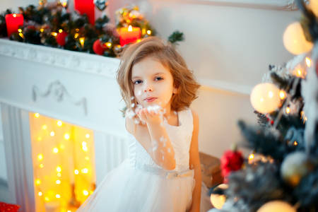 Cute little girl in white tender beautiful dress standing in brightly decorated room, near Christmas tree, full of decoration, blowing snow from hand. Stock fotó