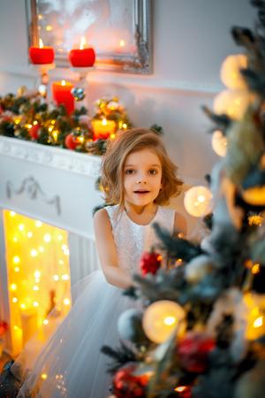 Smiling little girl peeping from behind Christmas tree in living room. Vertical indoors shot 写真素材