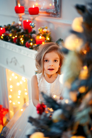 Smiling little girl peeping from behind Christmas tree in living room. Vertical indoors shot Stock Photo