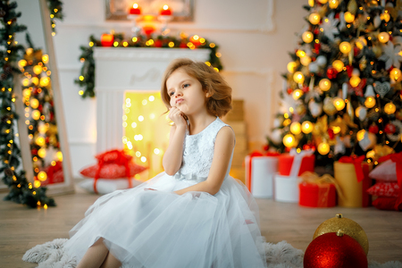Thoughtful cute little girl in white dress sitting in room decorated for Christmas. Banco de Imagens