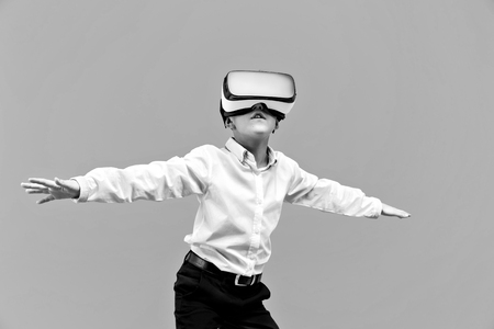 Kid in formal outfit wearing VR glasses putting hands out in excitement isolated on grey background.
