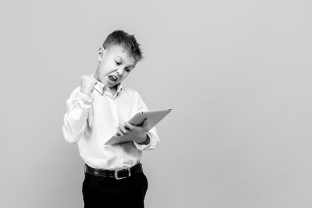 Happy young boy in formal clothing using tablet. Studio shot isolated on gray. Winner. Stock Photo