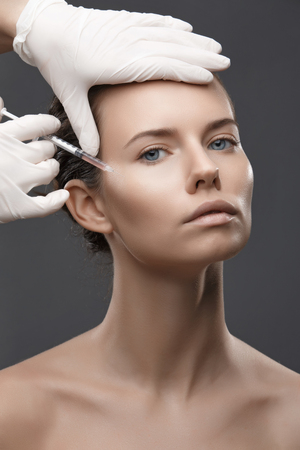 Portrait of young woman getting cosmetic injection. Clean Beauty.  Opened eyes. Stock Photo