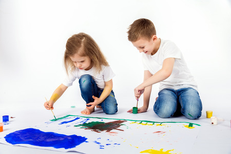 Two pretty child friends boy and girl in white shirts and blue jeans, trendy hair style, barefoot, drawing pictures on white sheet of paper by paints isolated on white. Studio shot.
