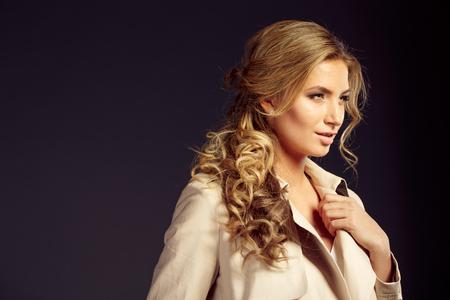 sexy girl with long blond hair in beige fur coat in studio