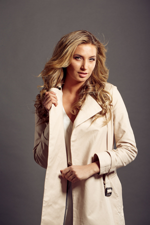 sexy girl with long blond hair in beige fur coat in studio