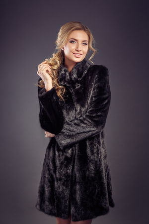 Fashion seductive blond hair lady in an elegant fur coat and black underwear on a dark background. Retouched. Stock Photo