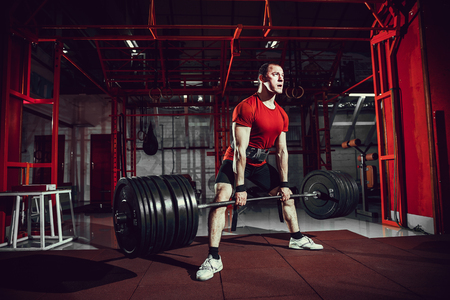 Muscular fitness man doing deadlift a barbell in modern fitness center. Functional training. Snatch exercise Stock Photo