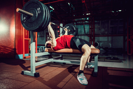 Very Strong man doing bench press workout in gym. Stock Photo