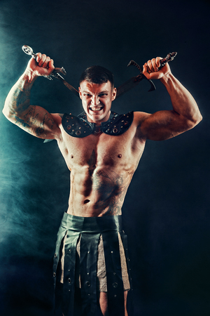 Portrait of handsome muscular gladiator with two swords. Studio shot. Black background. Scream.