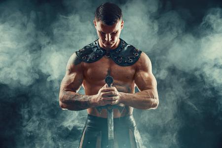 Portrait of handsome muscular gladiator with sword. Studio shot. Smoke on background.