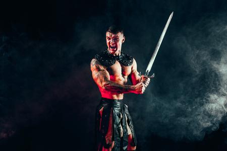 Portrait of handsome muscular gladiator with sword. Studio shot. Smoke on background. Scream.