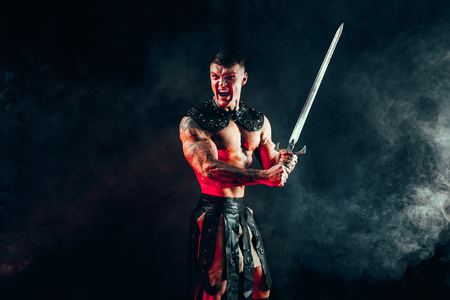 Portrait of handsome muscular gladiator with sword. Studio shot. Smoke on background. Scream.