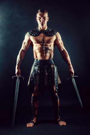 Portrait of handsome muscular gladiator with two swords. Studio shot. Black background.