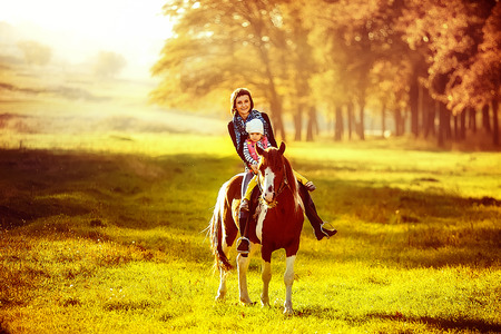 Little girl and her mother riding a horseback in the sunny meadow. Outdoors shot. Stock Photo