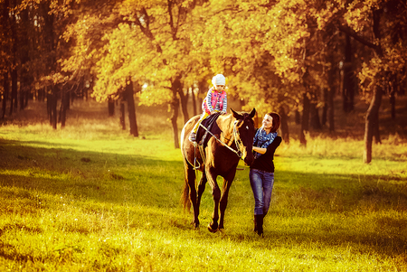 Little girl riding on a horseback with her mother walking nearby. Фото со стока
