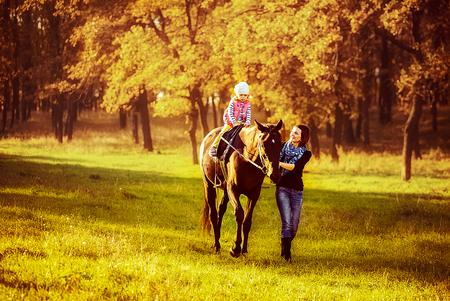 Meisje dat te paard met haar moeder berijdt die dichtbij loopt.