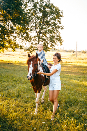 Little girl riding on a horseback with her mother walking nearby. Stock Photo