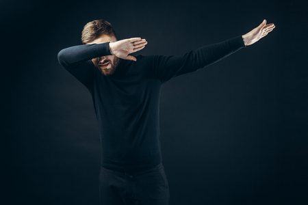 Anonymous man in black stylish outfit covering face with hands dancing on black backdrop. Stock Photo