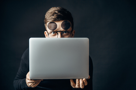 Young smart man wearing flip-up glasses covering face with laptop looking at camera. Stok Fotoğraf