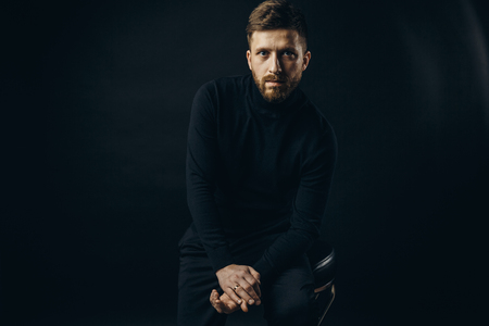 Bearded man wearing black looking unemotionally at camera on black background of studio. Stock Photo