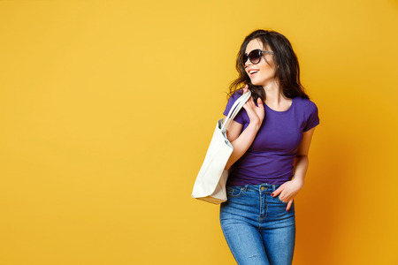 Beautiful young woman in sunglasses, purple shirt, blue jeans posing with bag on the wonderful yellow background Banco de Imagens