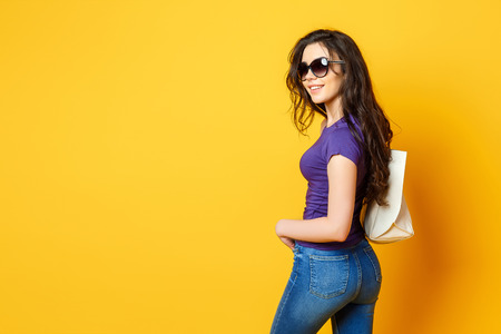 Beautiful young woman in sunglasses, purple shirt, blue jeans posing with bag on the wonderful yellow background Archivio Fotografico