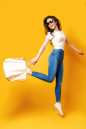 Beautiful young woman in sunglasses, white shirt, blue jeans posing, jumping with bag on the yellow background 免版税图像