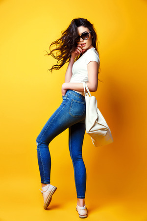 Beautiful young woman in sunglasses, white shirt, blue jeans posing with bag on the yellow background Archivio Fotografico
