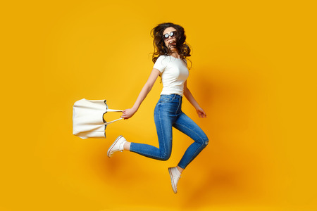 Beautiful young woman in sunglasses, white shirt, blue jeans posing, jumping with bag on the yellow background Archivio Fotografico