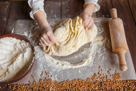 Szczegóły rąk wyrabiania ciasta na drewnianym stole