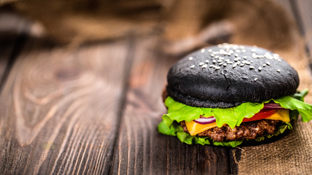 Close up of Homemade Black Burger with Cheese. Cheeseburger with black bun on dark wooden background. Junk food.