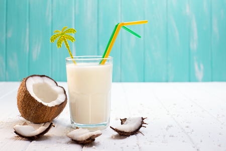 Glass of coconut milk on white wooden table. Selective focus Foto de archivo