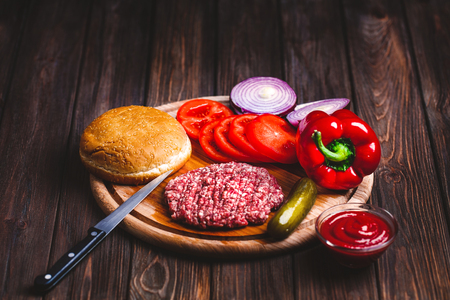 Raw Ground beef meat Burger steak cutlets with seasoning, cheese, tomatoes, salad and bun on vintage wooden boards Stock Photo